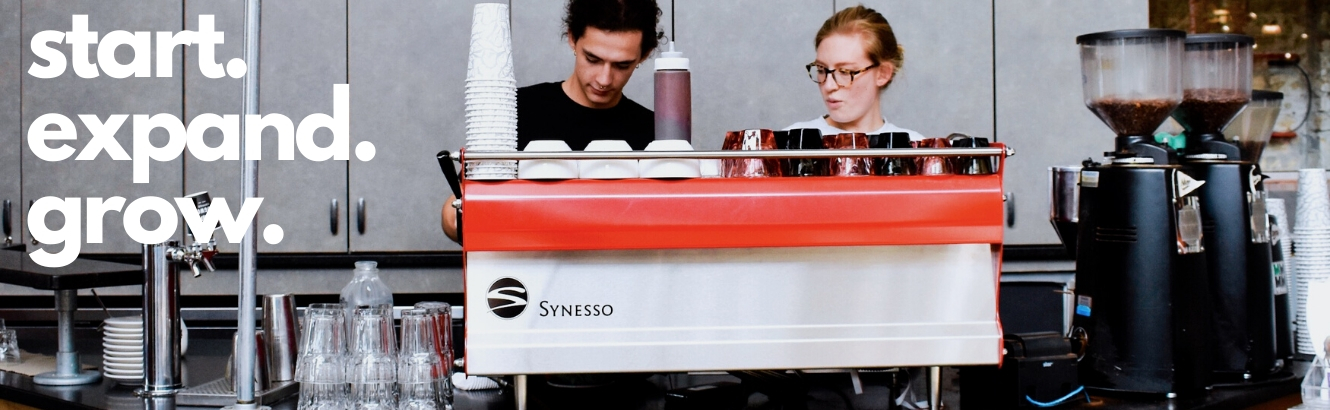"Baristas working at the espresso machine. Text says ""start. expand. grow."""